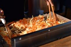 El cocinero prepara verduras fritas Fotografía de archivo