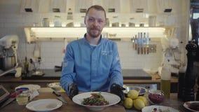 El cocinero presenta un plato recién preparado de los tallarines y de las verduras del alforfón en fondo de la cocina profesional almacen de video