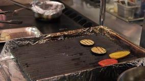 El cocinero presenta verduras de la parrilla de la bandeja de la hornada en restaurante moderno grande almacen de video