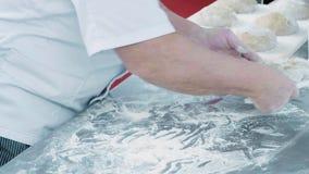 El cocinero profesional del confitero aplaude sus manos y el polvo vuela, harina Concepto: la producción de dulces almacen de metraje de vídeo