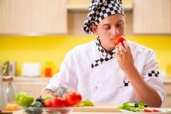 El cocinero profesional joven que prepara la ensalada en la cocina imagen de archivo
