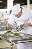 El cocinero profesional prepara el plato de la carne en el restaurante Imagen de archivo