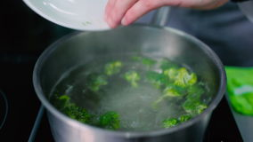 El cocinero puso el bróculi en el agua hervida almacen de video