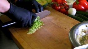 El cocinero que cocina las manos del cocinero del corte del restaurante de la cocina de la comida en hotel negro de los guantes s almacen de metraje de vídeo