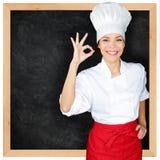 El cocinero que muestra la pizarra del menú y la mano perfecta firman Imágenes de archivo libres de regalías