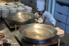 El cocinero se prepara para cocinar el aceite en wok en la cocina comercial Imagenes de archivo