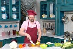 El cocinero serio en delantal rojo y capo rojo en la cocina corta verduras Imagen de archivo