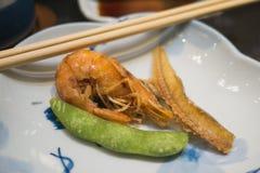 El cocinero sirve cuidadosamente el menú frito del camarón para servir como aperitivo para los clientes fotos de archivo libres de regalías