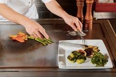 El cocinero sirve la comida en una placa Imagen de archivo