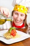 El cocinero sonriente adorna un plato italiano de las pastas Imágenes de archivo libres de regalías