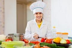 El cocinero sonriente trabaja con el tomate y otras verduras Imagen de archivo