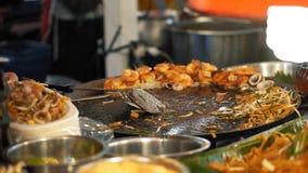 El cocinero tailandés es tallarines tailandeses del cojín de la preparación con los brotes y los mariscos Comida sabrosa de la ca metrajes