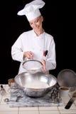El cocinero tamiza la harina de la torta Imagen de archivo