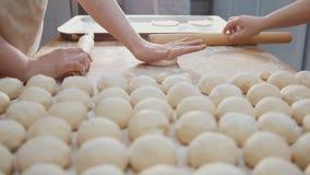 El cocinero tamiza la harina y el azúcar que adorna las empanadas en la panadería Imagen de archivo