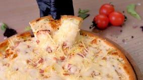 El cocinero toma una rebanada de pizza del tocino con el queso derretido, manos en la opini?n de goma del primer de los guantes metrajes
