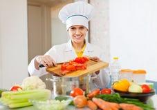El cocinero trabaja con el tomate y otras verduras Foto de archivo libre de regalías