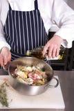El cocinero vierte el aceite de oliva Imagen de archivo