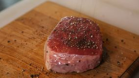 El cocinero vierte el filete de carne de vaca de los cristales de la pimienta negra almacen de video