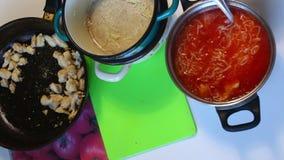 El cocinero vierte la sal en una cuchara de sopa y añade a la sopa cocinada del tomate Después de eso, mezcla a fondo el plato pr almacen de metraje de vídeo