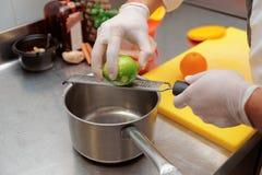 El cocinero zesting la cal, cocina comercial Foto de archivo