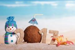 El coco en lugar de otro numera 0 en la cantidad 2017, muñeco de nieve contra el mar Fotos de archivo