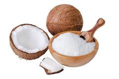 El coco forma escamas en un cuenco de madera con la cucharada aislada en blanco Fotografía de archivo libre de regalías