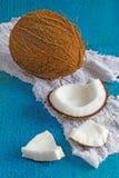 El coco y el coco junta las piezas con el paño blanco en el fondo de madera Fotografía de archivo