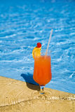 El coctel anaranjado se coloca en el borde de la piscina. Imagen de archivo
