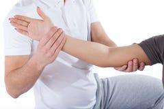 El codo de la mujer de examen del doctor de la fisioterapia Foto de archivo