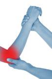El codo dolorido, mano, mostrada rojo, mantiene dado imagen de archivo