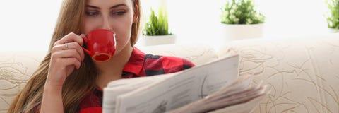 El coffe de consumición de la mujer y la lectura se sientan en el sofá imagen de archivo libre de regalías