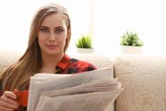 El coffe de consumición de la mujer y la lectura se sientan en el sofá imágenes de archivo libres de regalías