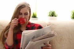 El coffe de consumición de la mujer y la lectura se sientan en el sofá foto de archivo