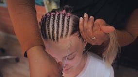 El coiffeur afroamericano del peluquero teje las trenzas francesas, el peinado de la novia almacen de metraje de vídeo