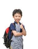 El colegial con sonrisas de la mochila y la demostración manosean con los dedos para arriba Imagen de archivo libre de regalías