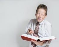 El colegial de risa lee un libro rojo grande Fotografía de archivo libre de regalías