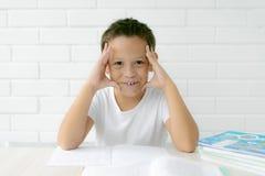 El colegial del muchacho enseña a lecciones que escribe en cuaderno y libros de lectura imagenes de archivo