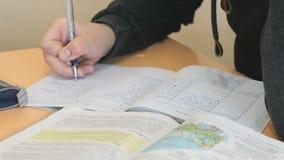 El colegial escribe el texto en libro de ejercicio en la lección almacen de video
