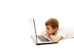 El colegial joven está mintiendo en suelo con una computadora portátil Foto de archivo libre de regalías