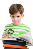 El colegial lee el libro con la lupa Imagenes de archivo