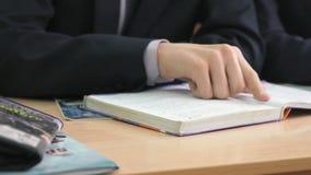 El colegial mueve de un tirón las páginas del libro de escuela Cierre para arriba almacen de metraje de vídeo