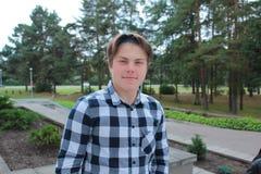 El colegial o el estudiante del adolescente del muchacho se está colocando en las escaleras en una camisa, sonriendo, mochila roj Imágenes de archivo libres de regalías