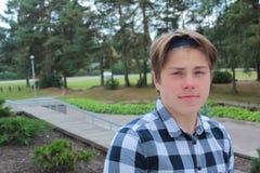 El colegial o el estudiante del adolescente del muchacho se está colocando en las escaleras en una camisa, sonriendo, mochila roj Fotos de archivo libres de regalías