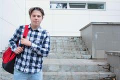 El colegial o el estudiante del adolescente del muchacho se está colocando en las escaleras en una camisa, sonriendo, mochila roj Fotos de archivo