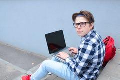 El colegial o el estudiante del adolescente del muchacho se está sentando en las escaleras, trabajando en el ordenador, los vidri Foto de archivo libre de regalías