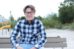 El colegial o el estudiante en una camisa, sonrisas del adolescente del muchacho en vidrios, escucha la música en el teléfono Fotos de archivo