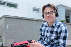 El colegial o el estudiante en una camisa, sonrisas del adolescente del muchacho en vidrios, escucha la música en el teléfono Foto de archivo