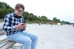 El colegial o el estudiante en una camisa, sonrisas del adolescente del muchacho en vidrios, escucha la música en el teléfono Fotografía de archivo