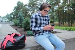 El colegial o el estudiante en una camisa, sonrisas del adolescente del muchacho en vidrios, escucha la música en el teléfono Imágenes de archivo libres de regalías