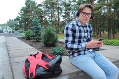El colegial o el estudiante en una camisa, sonrisas del adolescente del muchacho en vidrios, escucha la música en el teléfono Imagenes de archivo